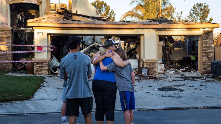 ANHEIM HILLS, CA - OCTOBER 10, 2017: Neighbors console each other in front of one of 6 homes that bu