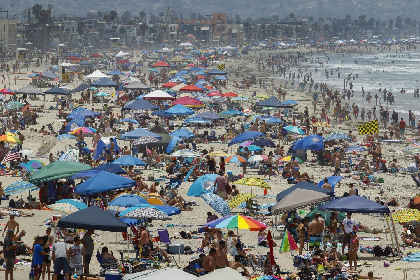 The view from the top of the main lifeguard tower in Pacific Beach shows thousands of people, with their towels, umbrellas, and canopies, covering the beach at Pacific Beach south to Mission Beach on the 4th of July in San Diego on Friday.