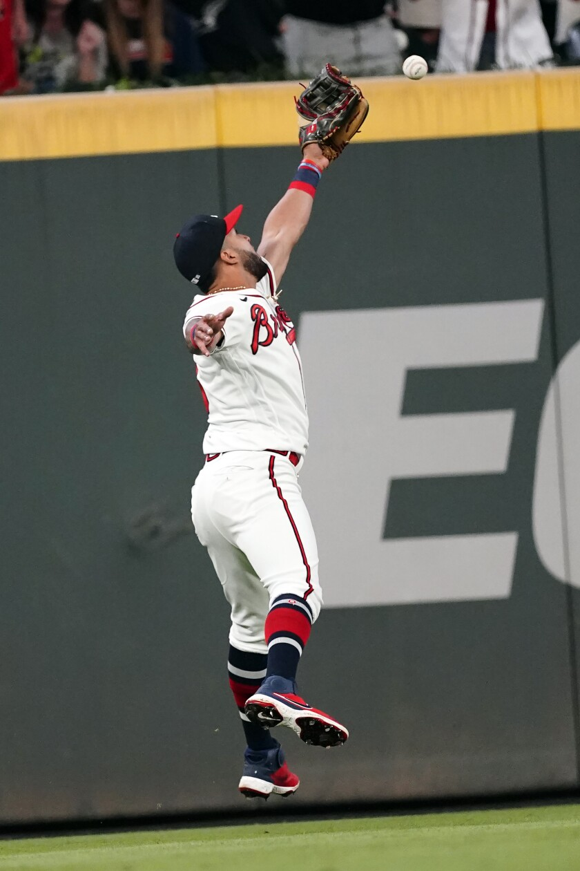 A flyball from Philadelphia Phillies' Matt Vierling gets past Atlanta Braves left fielder Eddie Rosario (8) in the ninth inning of a baseball game Tuesday, Sept. 28, 2021, in Atlanta. Rosario was charged with an error. (AP Photo/John Bazemore)