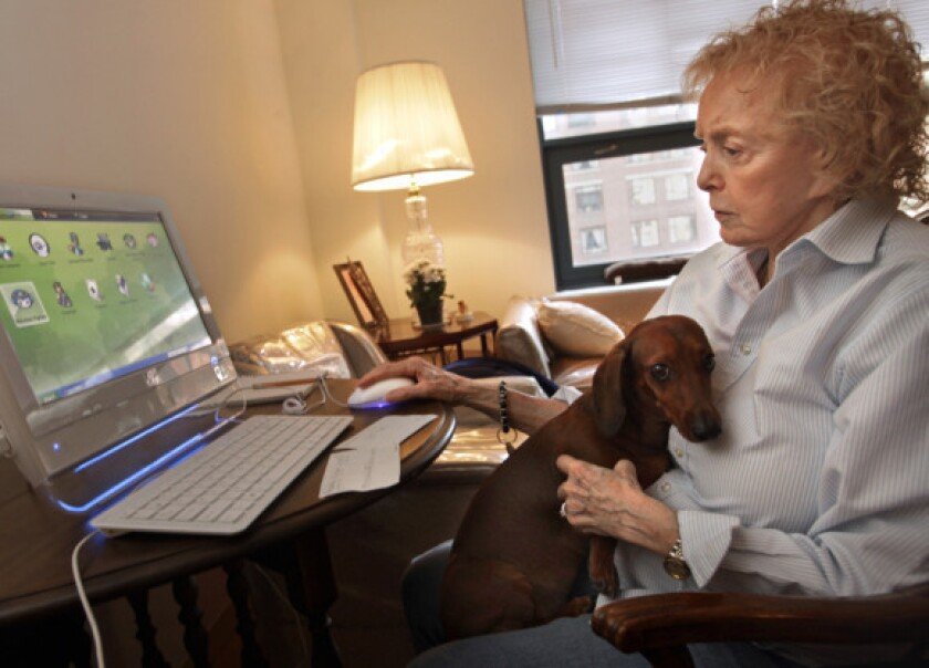 Rosemary Nickola works on her computer with her dog, Delilah, on her lap in her New York apartment in February. At that time, Nickola was struggling with technology, but this week she earned a certificate after completing a computer course.