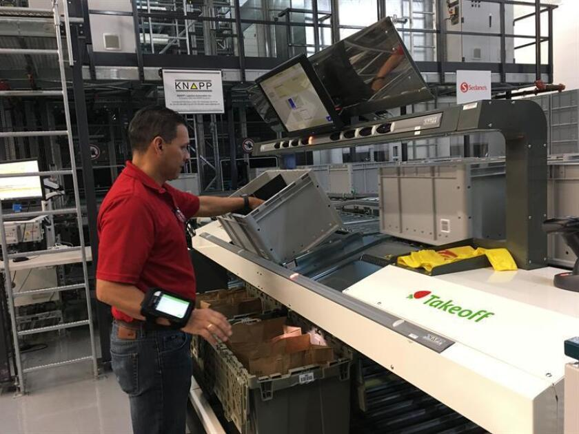Un empleado de un supermercado Sedano's en Miami (Florida) trabaja hoy en la nueva plataforma automatizada para agilizar la recogida y embalaje de productos para la venta por internet que evita a sus empleados recorrer los pasillos y estantes de las tiendas y ahorra tiempo a sus clientes. EFE