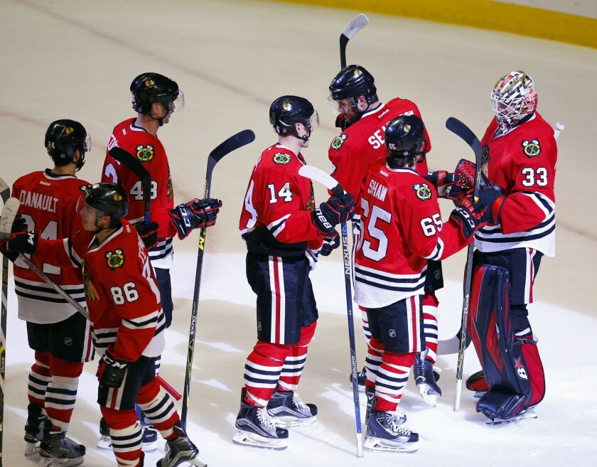 Chicago Blackhawks goalie Scott Darling (33) celebrates with teammates after a NHL hockey game against the Toronto Maple Leafs Monday, Feb. 15, 2016, in Chicago. The Blackhawks won the game 7-2. (AP Photo/Jeff Haynes)