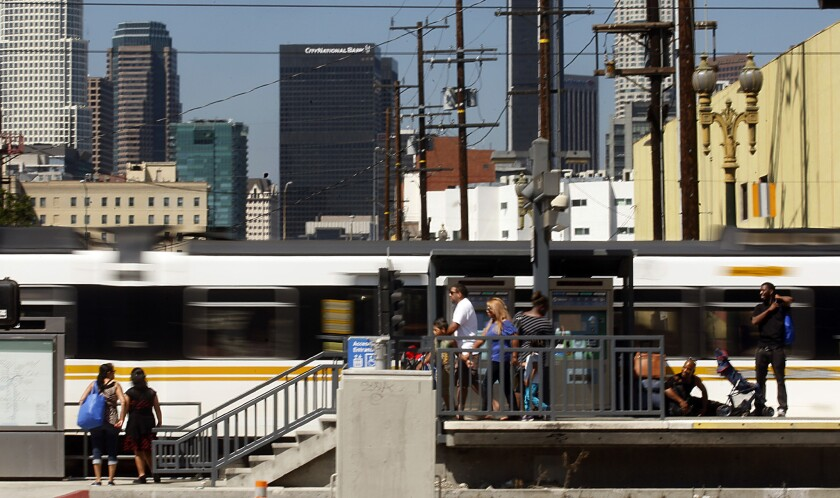 Metro Blue Line cars zip past a station near the intersection of Washington Boulevard and Flower Street, where the Blue Line converges with the Expo Line.