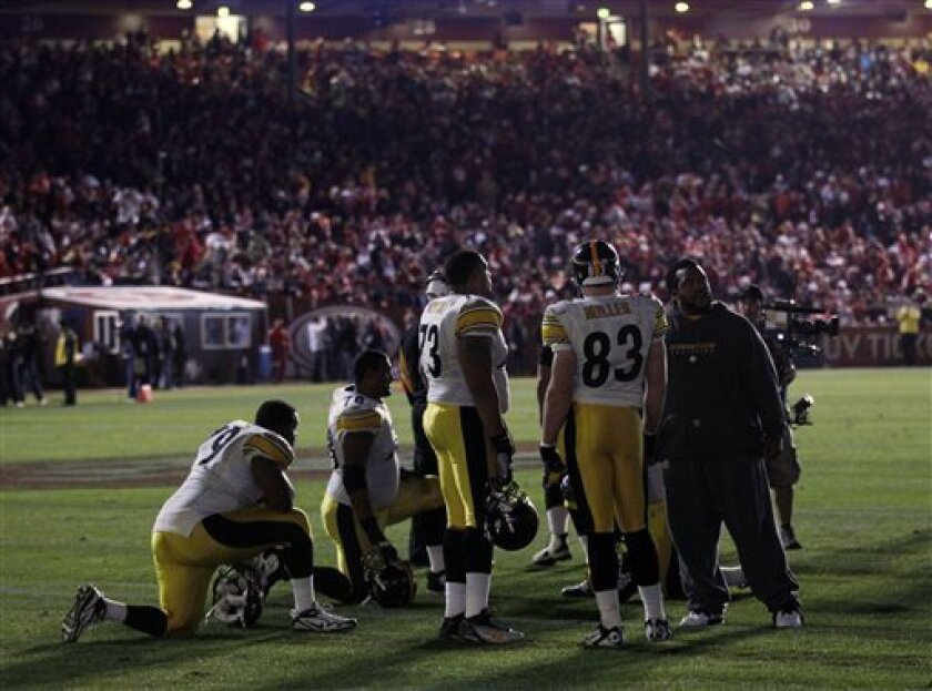 Members of the Pittsburgh Steelers wait on the field during a second power outage, in the second quarter of the Steelers' NFL football game against the San Francisco 49ers in San Francisco, Monday, Dec. 19, 2011. (AP Photo/Marcio Jose Sanchez)