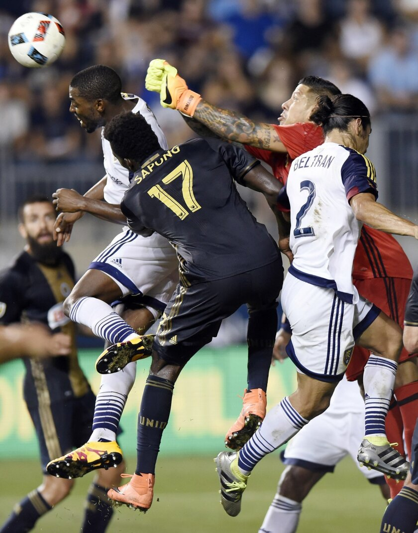 Real Salt Lake goalie Nick Rimando (18) makes a save over Philadelphia Union's C.J. Sapong (17) during the second half of an MLS soccer match Sunday, July 31, 2016, in Chester, Pa. Real Salt Lake beat the Union 2-1. (AP Photo/Michael Perez)