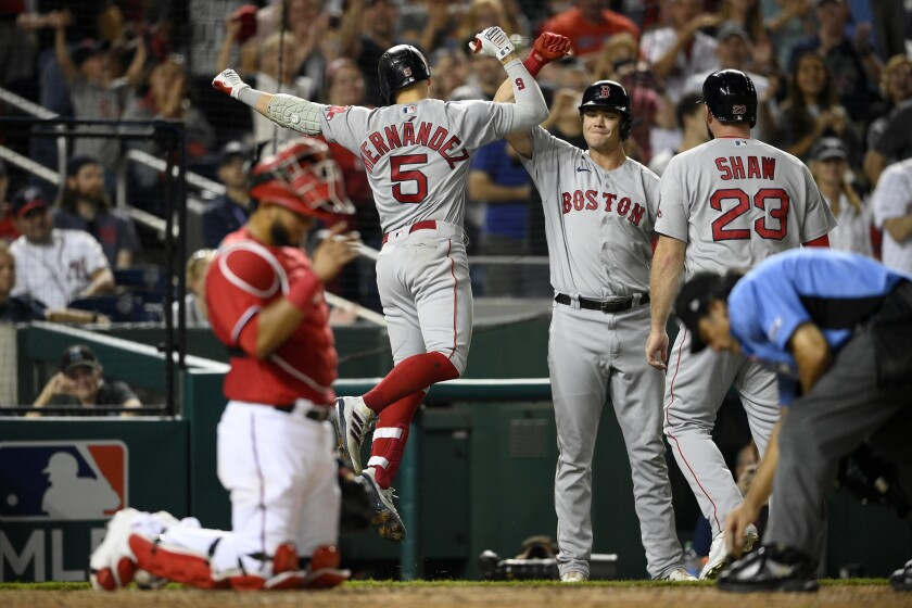 Boston Red Sox's Enrique Hernandez (5) celebrates his two-run home run with Bobby Dalbec, second from right, and Travis Shaw (23) during the ninth inning of a baseball game Saturday, Oct. 2, 2021, in Washington. Washington Nationals catcher Keibert Ruiz is at from left. The Red Sox won 5-3.(AP Photo/Nick Wass)
