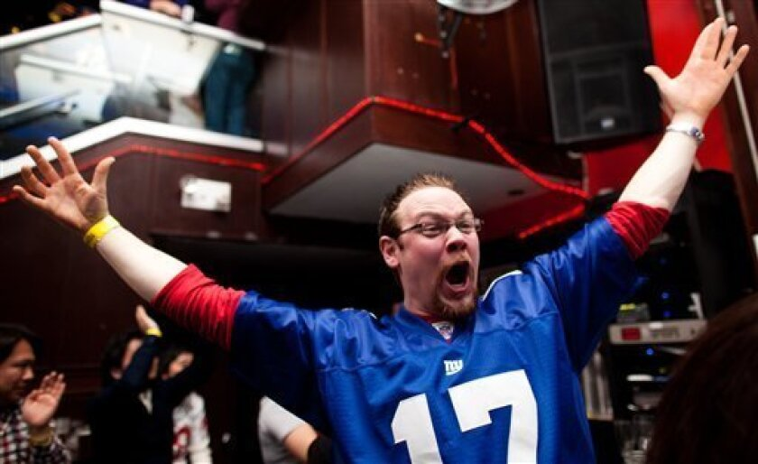 New York Giants fan Eddy Ruish, of Niagra Falls, Ontario, reacts while watching the broadcast of the NFL football Super Bowl between the New York Giants and the New England Patriots, in a midtown Manhattan bar, Sunday, Feb. 5, 2012, in New York. (AP Photo/John Minchillo)