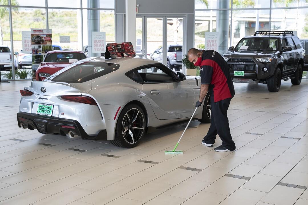 Gustavo Gutierrez mops the showroom floor with disinfectant at reopened Ventura Toyota.
