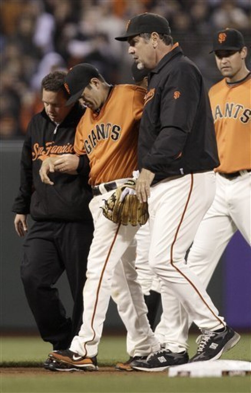 San Francisco Giants second baseman Freddy Sanchez, center, is helped off the field by a trainer and Bruce Bochy, right, after being injured fielding a base hit by Cincinnati Reds' Brandon Phillips in the fifth inning of a baseball game in San Francisco, Friday, June 10, 2011. (AP Photo/Jeff Chiu)