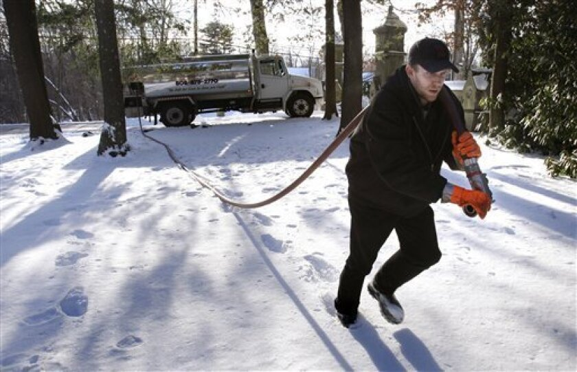 Jason Kilpatrick of Wholesale Fuel hauls a hose across a snow covered yard while delivering home heating oil in Framingham, Mass., Tuesday, Jan. 5, 2010. A private trade group said Wednesday, Jan. 6, a measure tracking the U.S. service sector returned to growth last month, but the slight expansion wasn't enough to kick-start hiring.(AP Photo/Charles Krupa)
