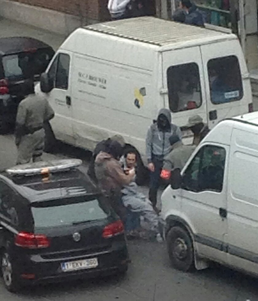 In this Friday, March 18, 2016 photo made available Monday March 21, an unidentified man believed to be connected to key suspect in the November 2015 Paris attacks Salah Abdeslam, is detained by police during a raid in the Molenbeek neighborhood of Brussels, Belgium. Abdeslam was arrested Friday March 18, in Molenbeek after a four-month manhunt, and investigators are known to be still hunting for other suspects on their wanted list. (AP Photo/Zouheir Ambar)