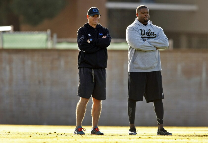 UCLA offensive line coach Adrian Klemm, right, was reinstated by the university Friday following a suspension for alleged NCAA violations.