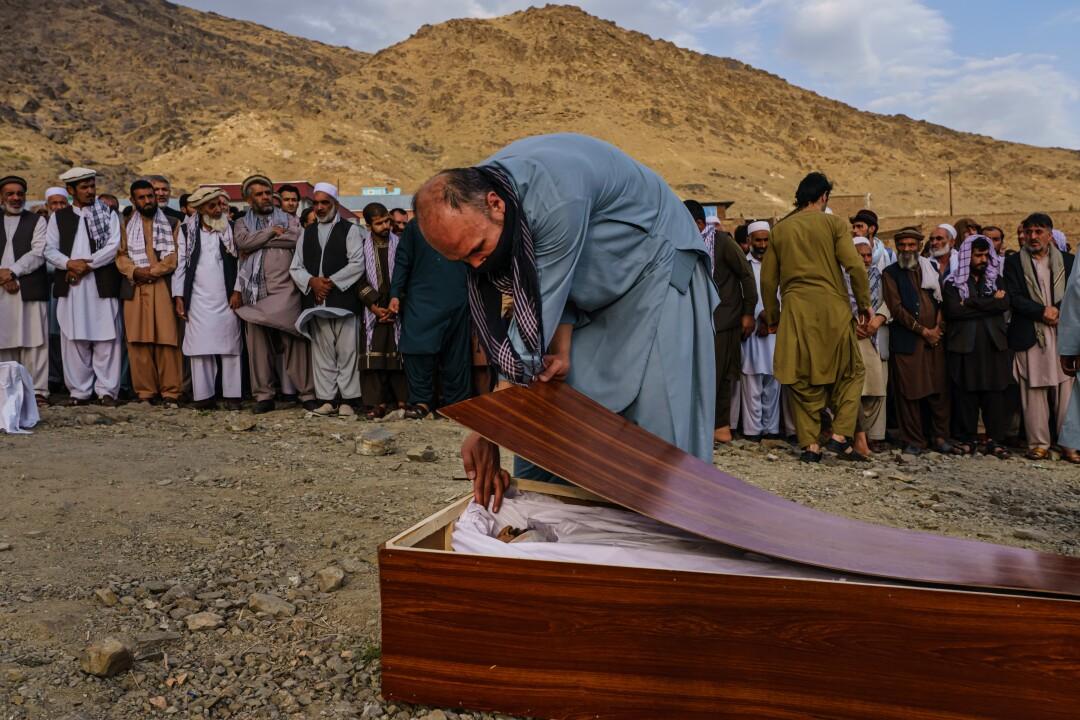 A man bids farewell to Zamari Ahmadi in his casket during Monday's mass funeral in Kabul.