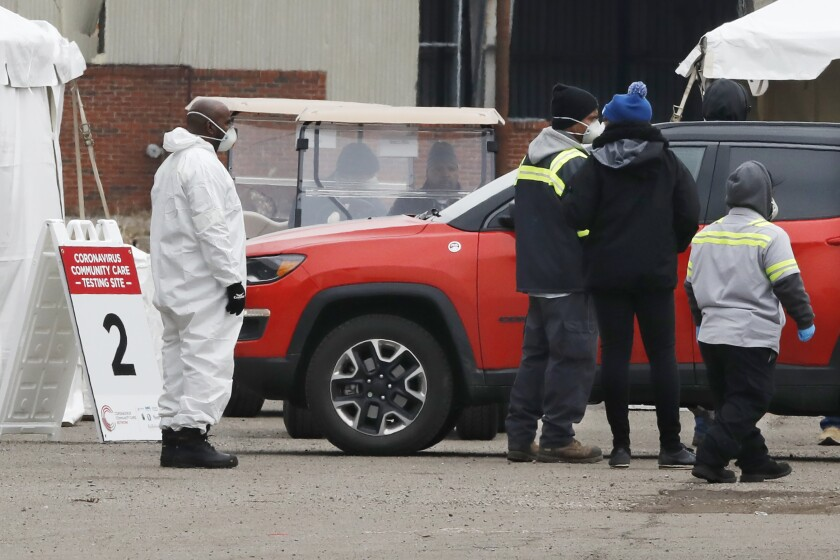 Healthcare officials watch as a vehicle approaches a testing site at the Michigan State Fairgrounds last week. Detroit set up several stations at the fairgrounds to allow for drive-up testing for the coronavirus.