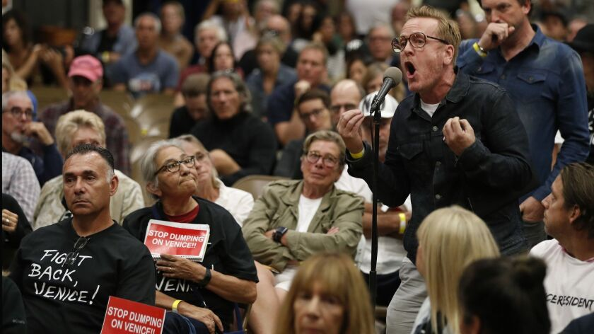 Anthony Wells, right, voices his opposition to Mayor Eric Garcetti, Councilman Mike Bonin and LAPD Police Chief Michel Moore during a town hall at Westminster Elementary School in Venice, Calif. on Oct. 17.