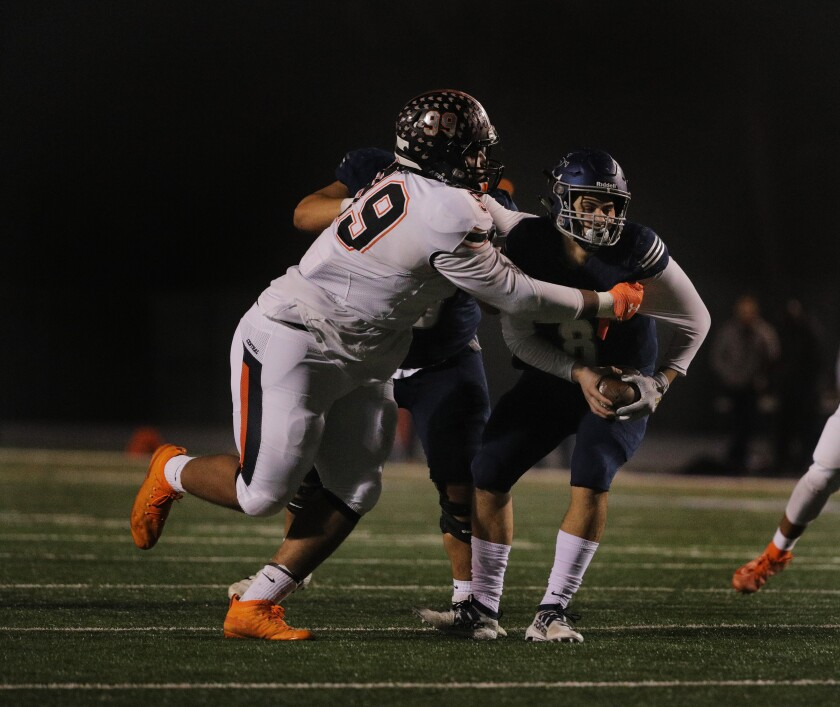 Fresno Central defensive lineman Ricky Correia sacks Sierra Canyon quarterback Chayden Peery during the Division 1-AA championship game at Cerritos College on December 13, 2019.