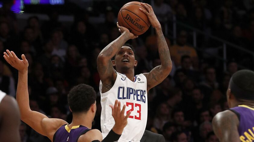 LOS ANGELES, CALIF. - DEC. 28, 2018. Clippers guard Lou Williams shoots over Lakers guard Josh Har