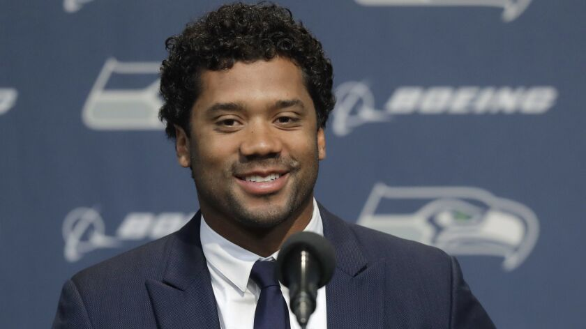 Seattle Seahawks NFL football quarterback Russell Wilson talks to reporters Wednesday, April 17, 201