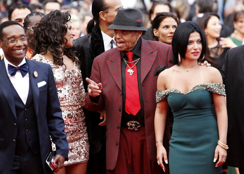Joe Jackson, center, and unidentified guests arrive for the screening of the film Sicario at the 68th international film festival, Cannes, southern France, Tuesday, May 19, 2015. (AP Photo/Lionel Cironneau)
