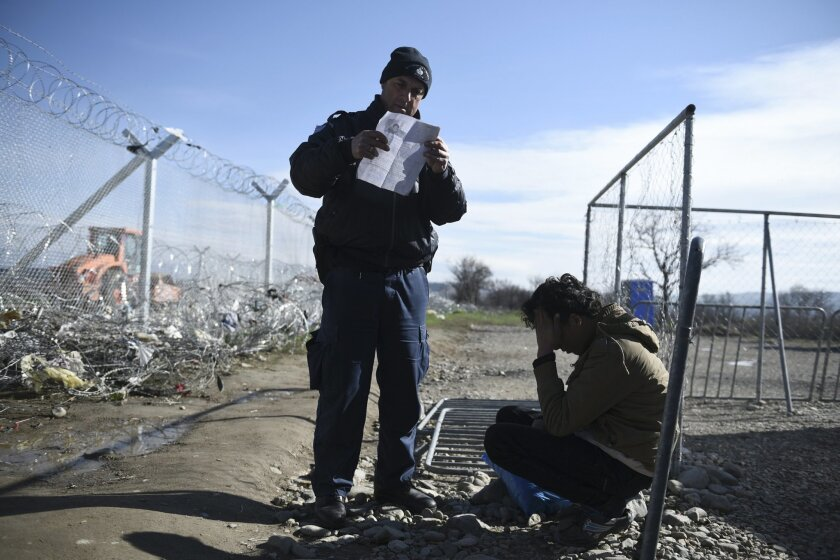 A Greek policeman checks documents of a man at the borderline with Macedonia near the northern Greek village of Idomeni, on Sunday, Feb. 21, 2016. Macedonia has closed its southern border with Greece to Afghan migrants, allowing only Iraqis and Syrians, Greek police report. (AP Photo/Giannis Papanikos)