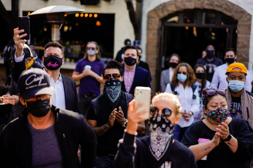 A crowd of people in face coverings clap and hold up phones at an outdoor news conference