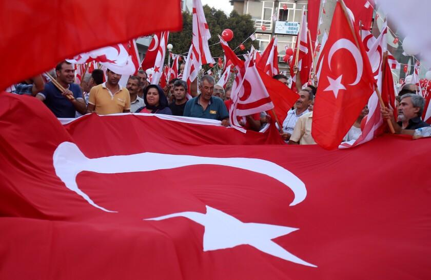 Manifestantes turco-chipriotas ondean banderas turcas y chipriotas durante una manifestación en apoyo del presidente turco, Recep Tayyip Erodgan, tras un intento de golpe de Estado, en la capital del lado turco de Chipre, Nicosia, el 5 de agosto de 2016. (AP Foto/Philippos Christou)