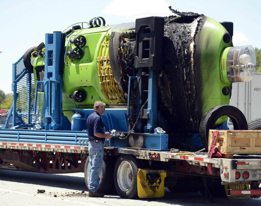 An investigator who declined to be identified looks over the damage to the Deepsea Challenger deep-diving submersible resting on its transport trailer in North Stonington, Conn. Thursday, July 23, 2015. The vessel was damaged by fire while being transported along I95 from Woods Hole to Baltimore. Filmmaker and ocean explorer James Cameron piloted the submersible in 2012 to a depth of nearly 35,800 feet (10,900 metres) in the deepest spot on the planet — the Mariana Trench near Guam. (Sean D. Elliot/The Day via AP) MANDATORY CREDIT