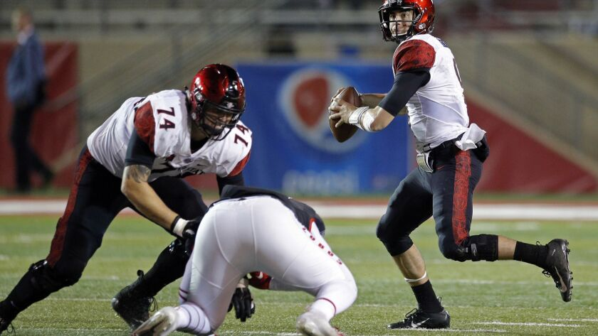 San Diego State quarterback Ryan Agnew, right, throws as offensive lineman Tyler Roemer (74) contain