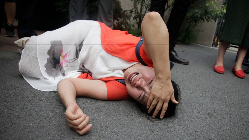 Fan Lili, the wife of imprisoned lawyer Gou Hongguo, lies on the ground in tears following an interaction with a plainclothes police officer outside the Tianjin No. 2 Intermediate People's Court in Tianjin, China, on Aug. 1.