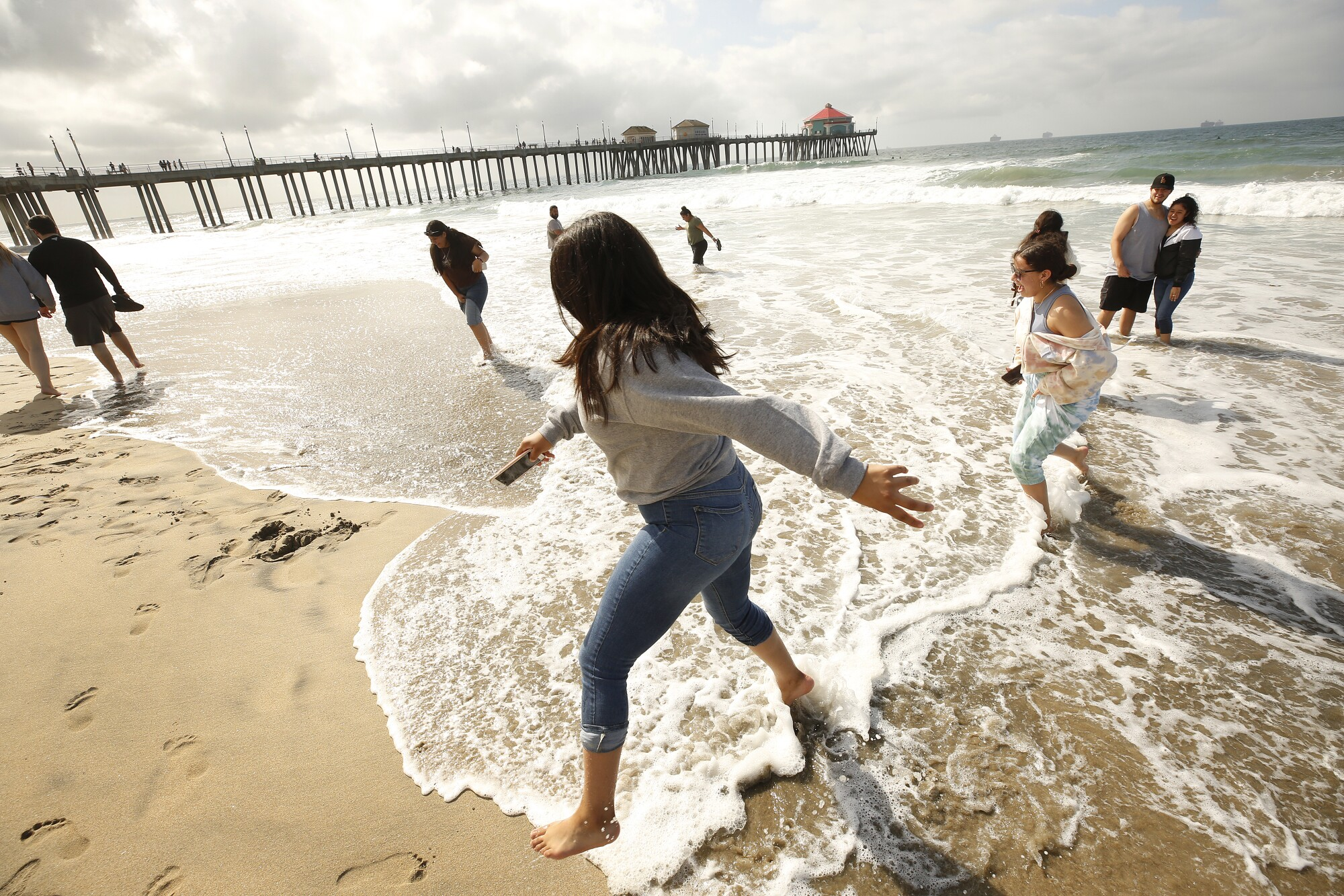 Destiny Corrales, left, and Hania Albarran, right, play in the surf north of the Huntington Beach Pier