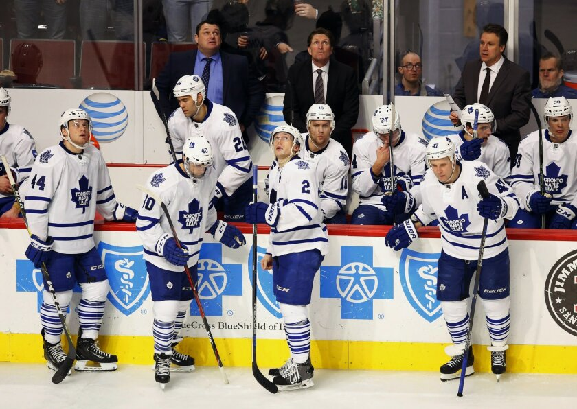 Toronto Maple Leafs head coach Mike Babcock, center back, and his team look at the scoreboard during the third period of an NHL hockey game against the Chicago Blackhawks Monday, Feb. 15, 2016, in Chicago. The Blackhawks won the game 7-2. (AP Photo/Jeff Haynes)