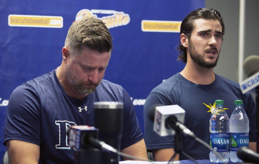 Montgomery Biscuits manager Morgan Ensberg, left, fights back tears as Ryan Thompson, a pitcher with the team, talks about teammate Blake Bivens during a news conference on Thursday.