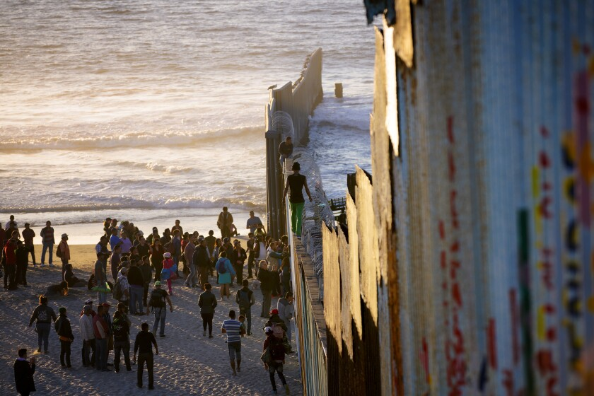 Migrants who arrived as part of a caravan from Central America to seek asylum in the U.S. gather at Playas de Tijuana