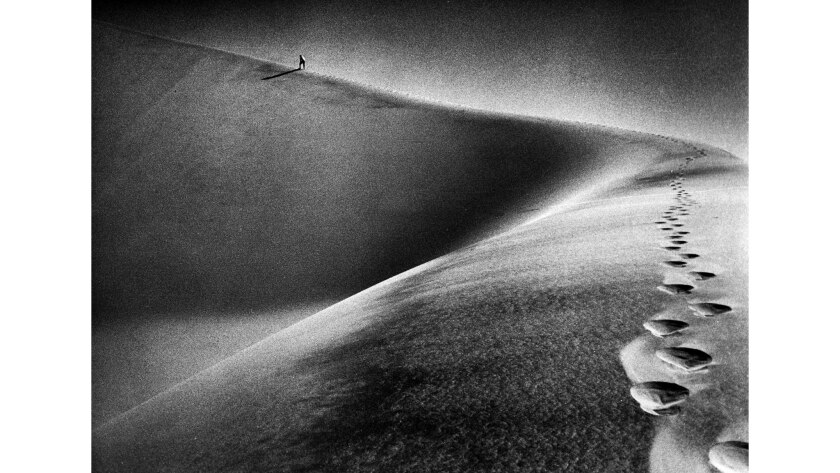 Oct. 16, 1976: Jack Hereford, in far background, makes his way up a ridge of the Kelso Dunes in the Mojave Desert during an investigation of mysterious sounds emanating there.