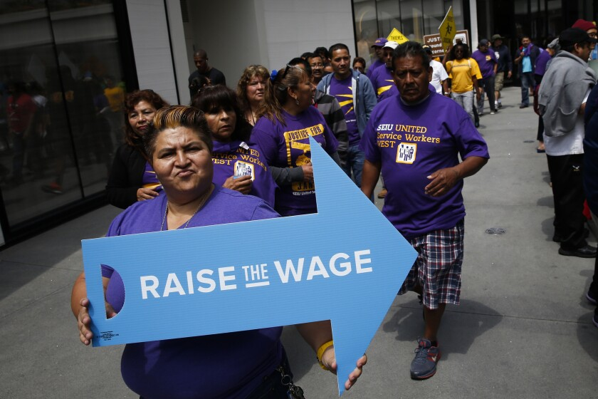 People protest downtown with the Los Angeles Wage Theft and Raise the Wage coalitions in support of a $15 an hour minimum wage Monday in Los Angeles.