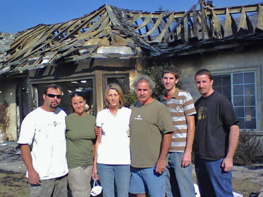 The Kunzes thought their Fallbrook house was fireproof, built with a steel frame instead of wood and with plaster three times the normal thickness. They stand in front of what's left of it: from left, son-in-law Jeremiah Boshard, daughter Jaime, mother Shari, father Glenn and sons Daniel and David.
