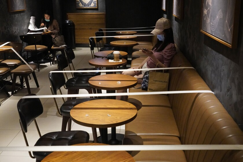 At a Starbucks in Hong Kong, tables and chairs are taped for the social distancing law enforcement to help curb the spread of the coronavirus.
