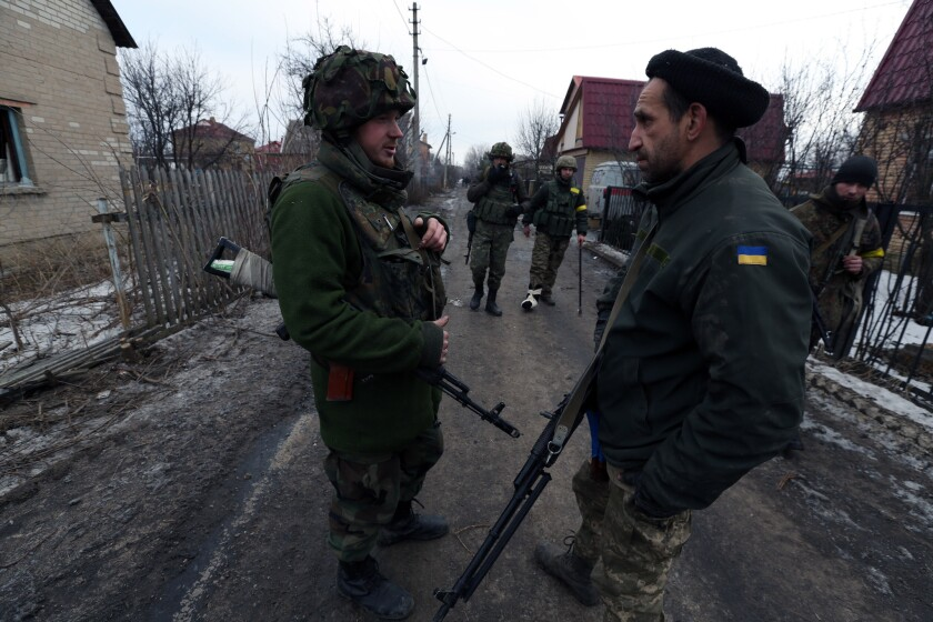 On the outskirts of Donetsk, Maxim Bugel, left, a Ukrainian platoon commander, talks to a survivor of the airport siege.