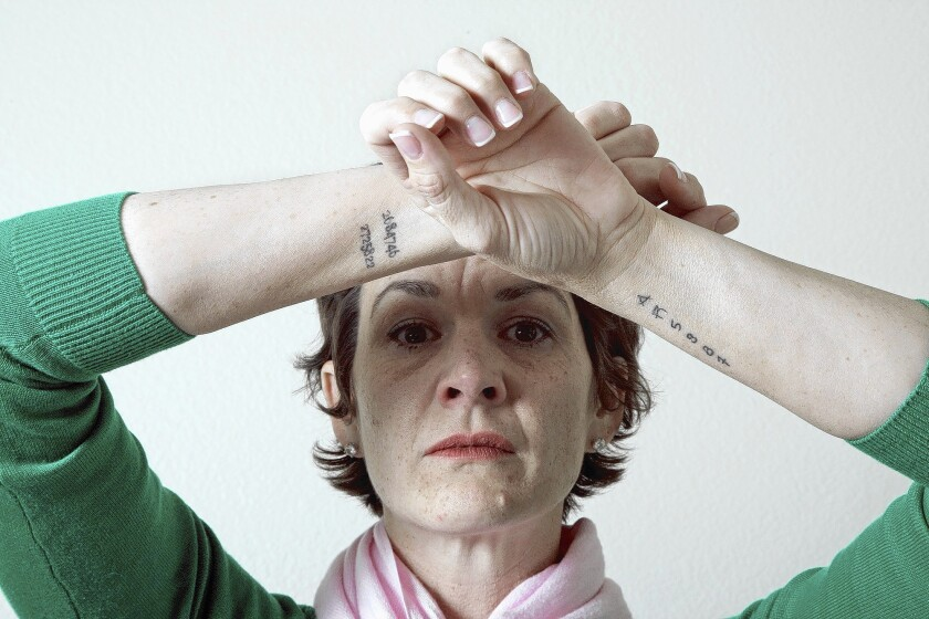 Jennifer Hoff of Ladera Ranch, whose mentally ill adult son is in prison for bank robbery, believes Laura's Law could have helped him and kept him out of prison. As in most of California, the law has not been implemented in Orange County. The tattoos on Jennifer's arms are her son's booking numbers from various arrests.
