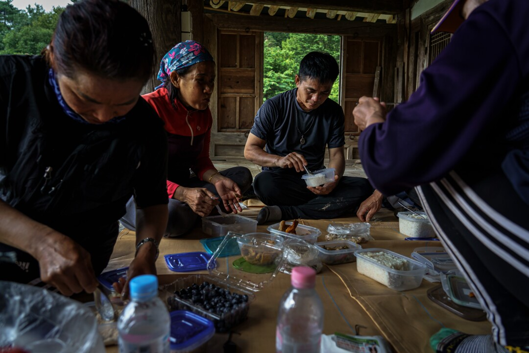 Promdeth Phonsrikaew, center, eats breakfast during a 15-minute break on a tobacco farm.