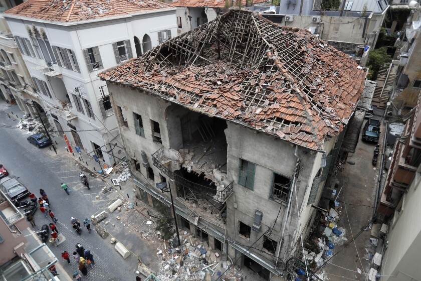 People pass in front of a house that was damaged during the last week's explosion that hit the seaport of Beirut, Lebanon, Tuesday, Aug. 11, 2020. (AP Photo/Hussein Malla)