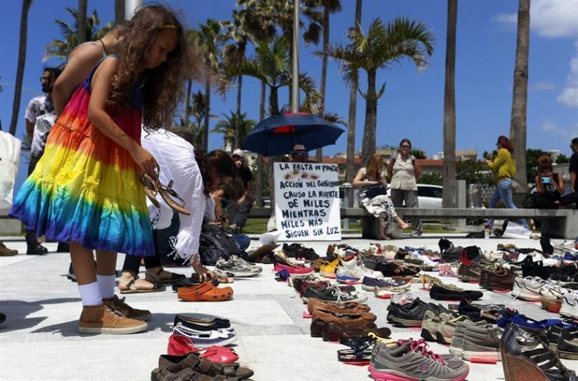 Una persona coloca unos zapatos en memoria a los muertos por el huracán María frente al Capitolio de San Juan, sede de la legislatura puertorriqueña (Puerto Rico). EFE/Archivo