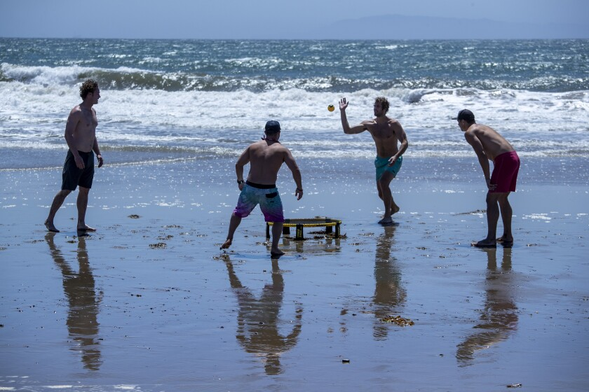 Friends play spikeball, a game perfect for social distancing, on an open but restricted San Buenaventura State Beach on Saturday in Ventura, Calif.