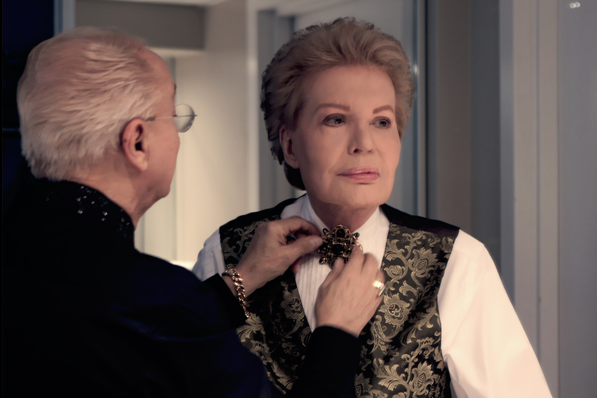 Willie Acosta, left, helps astrologer Walter Mercado get dressed for an event in Miami.