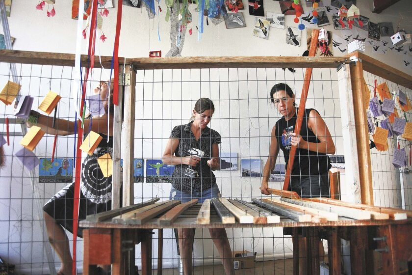 """Artists Stacie Birky-Greene, (from left), Terri Hughes-Oelrich and Lynn Susholtz work on """"Fence/Barda"""" at Art Produce Gallery. Misael Virgen/U-T"""