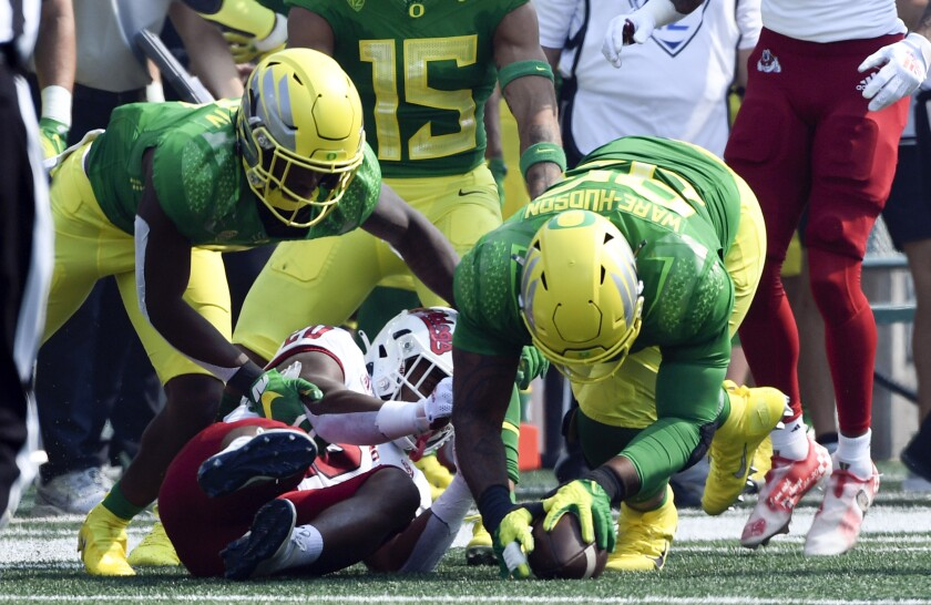 Oregon defensive tackle Keyon Ware-Hudson (95) recovers a fumble from Fresno State running back Ronnie Rivers (20) as Oregon safety Steve Stephens IV (7) comes in on the play during the first quarter of an NCAA college football game, Saturday, Sept. 4, 2021, in Eugene, Ore. (AP Photo/Andy Nelson)