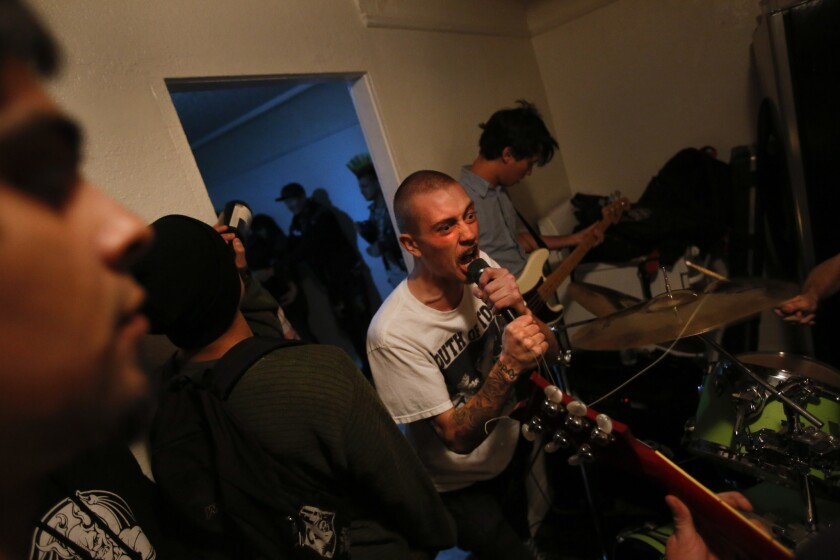 Chandler Herring, lead singer of The Testicle Difficulties, a punk band based in Orange County, sings in the cramped kitchen of a small home in the Florence district of South L.A.