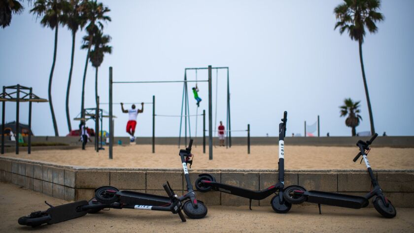 Westside vandals are waging a guerrilla war against pay-per-mile scooters. These Bird electric scooters were left on the Venice Beach boardwalk.