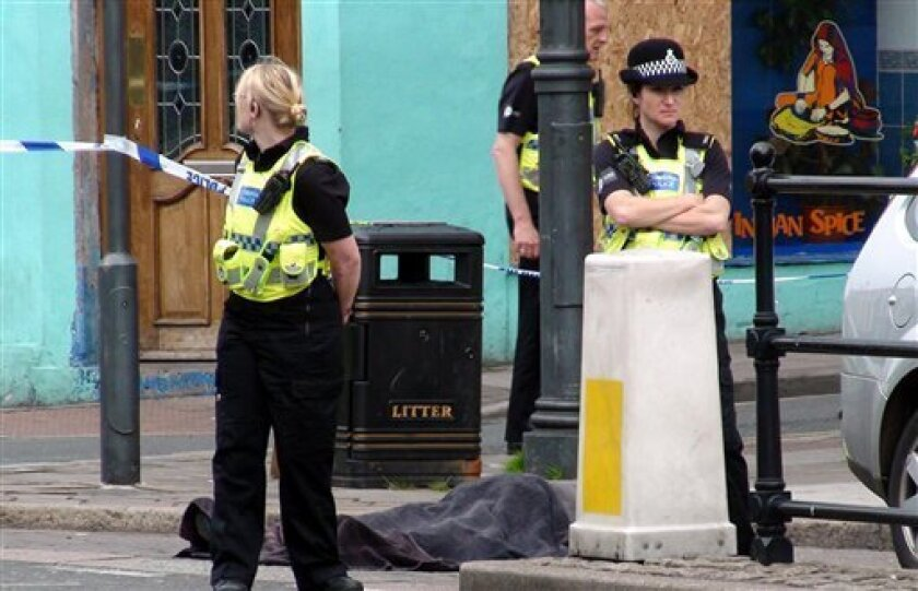 """Police stand next to a body following a shooting on Duke Street, in the town of Whitehaven in northwest England Wednesday June 2, 2010. British police were hunting down a man suspected in a shooting spree that has left more than one person dead in northwest England. The Cumbria Constabulary said there have been """"a number of fatalities"""" as well as several injuries after shots were fired in the town of Whitehaven and nearby Seascale and Egremont. (AP Photo/Rod Minchin/PA Wire)"""