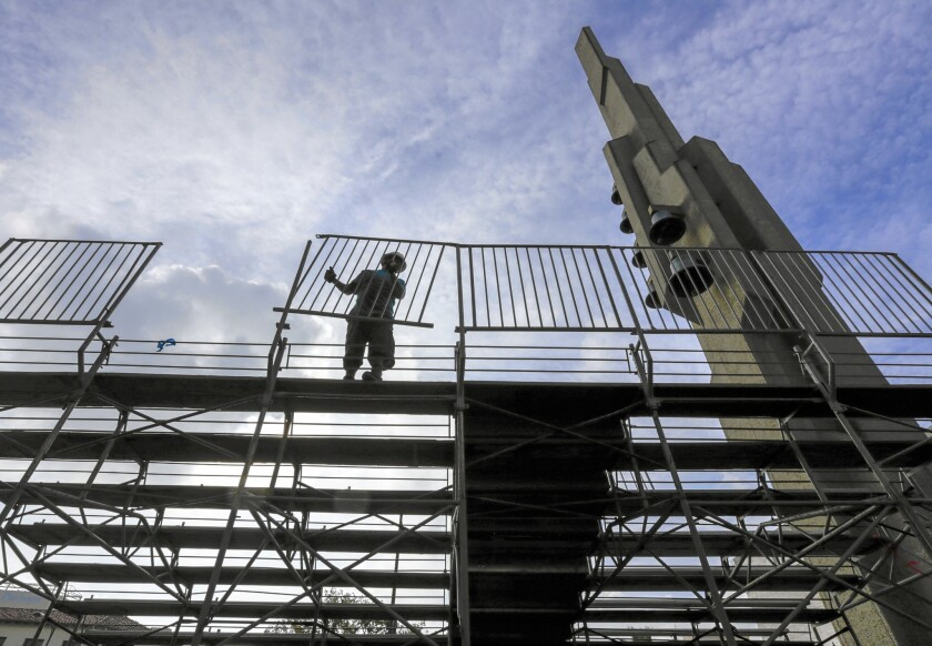 Jesus Esquivel installs a fence on bleachers in front of Gospel Siloam Church on Colorado Avenue in preparations for the Rose Parade in Pasadena.